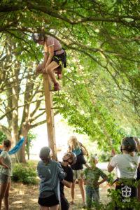 Pige klatrer på en pæl imens 2 andre holder den lodret for hende.